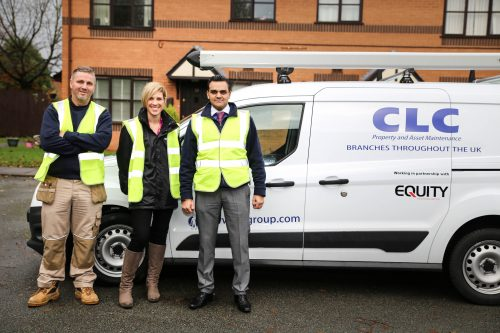 CLC employees pose in front of a CLC van