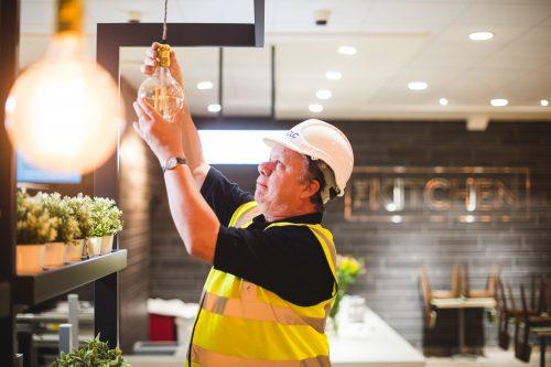 CLC worker fitting light in restaurant
