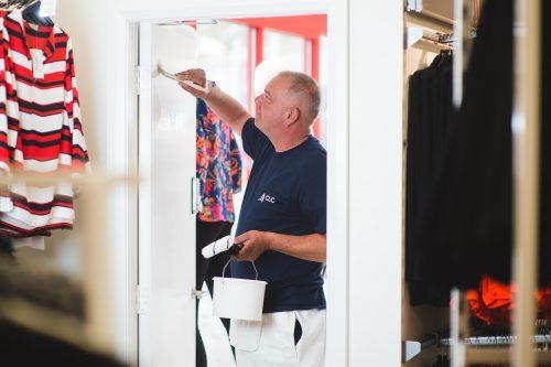 CLC worker painting door white