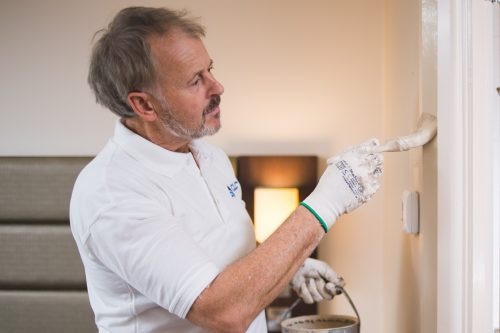 CLC worker painting interior of hotel room