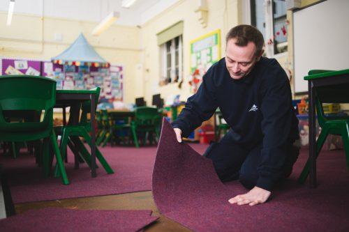 CLC employee fits a carpet