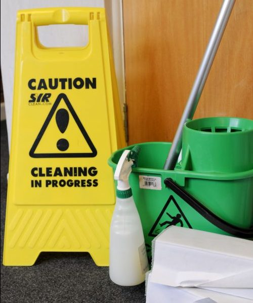 Office cleaning equipment with a yellow caution cleaning in progress warning sign, mop, bucket and paper towels